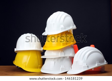 Stack of white and yellow helmets on black - stock photo