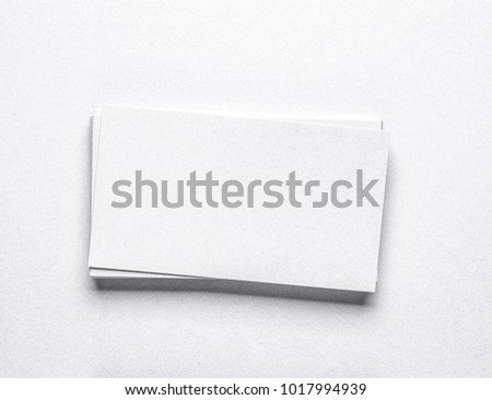 stack of white blank business cards on light background.