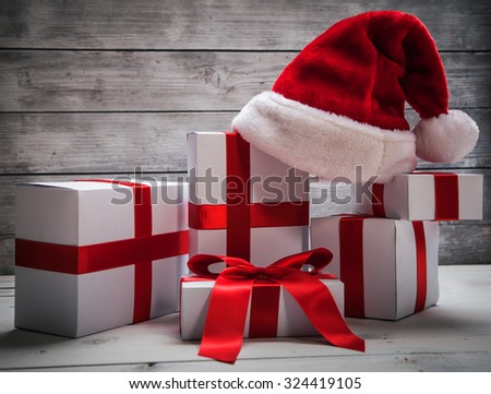Stack of white Christmas presents, with santa claus hat wooden background - stock photo