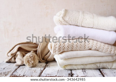 Stack of white cozy knitted sweaters on a wooden table  - stock photo