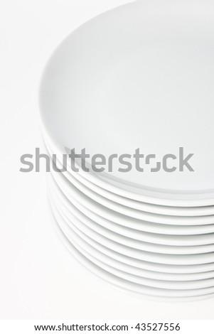 Stack of white plates on white background. - stock photo