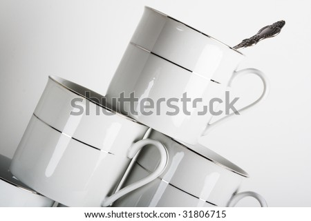Stack of white porcelain cups with the spoon in the top one