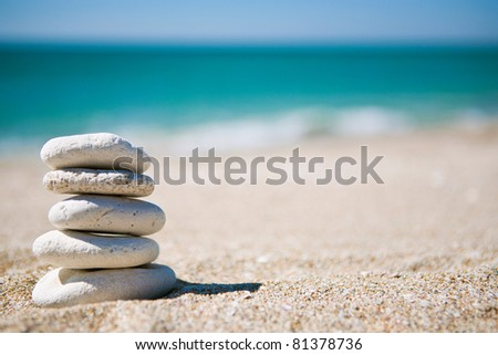 Stack of white stones on tropical beach - stock photo