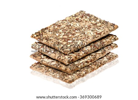 Stack of wholegrain crispy bread with sunflower, chia and sesames seeds on white background. - stock photo