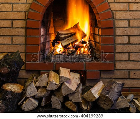 stack of wood and burning wood in indoor brick fireplace in country cottage - stock photo
