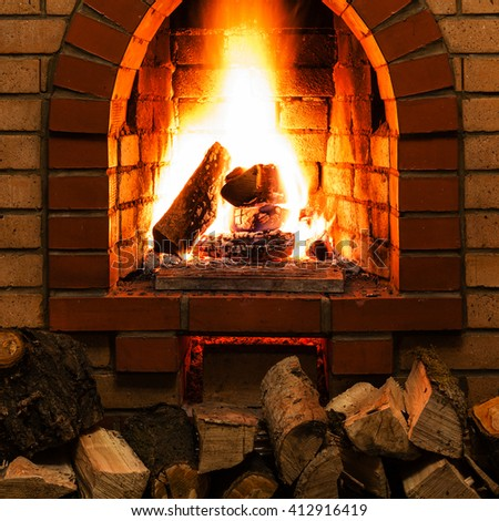 stack of wood and tongues of fire in indoor brick fireplace in country cottage - stock photo