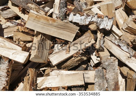 Stack of wood, chopped rough firewood on a yard.  - stock photo