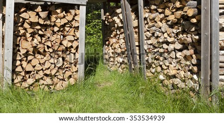 Stack of wood, chopped rough firewood on a yard. Green grass and wooden stay. - stock photo