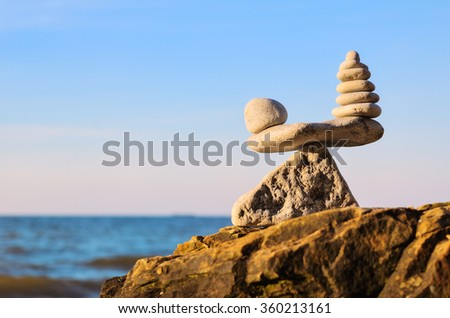 Stack of zen stones in balance at seashore - stock photo