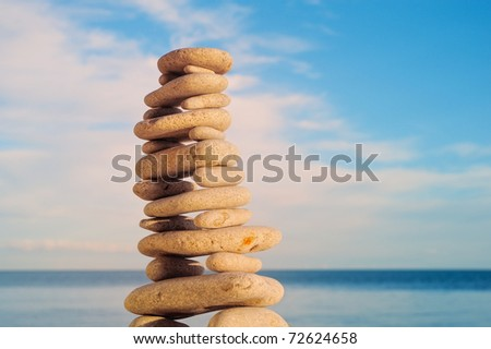Stack of zen stones on a sky and sea background - stock photo
