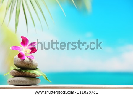 Stack of zen stones on sand beach - stock photo
