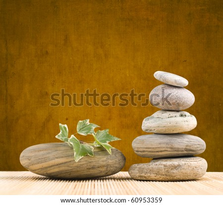Stack pebbles on bamboo table with grungy background - stock photo
