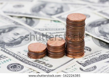 Stack US pennies in an ascending bar graph on background of money american hundred dollar bills - stock photo