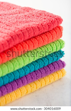 stacked bathroom towels in rainbow colors (yellow, purple, blue, green, orange, red), isolated over a white wood background, close up, vertical - stock photo