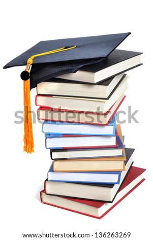 stacked books and a graduation hat with honor tassel - stock photo