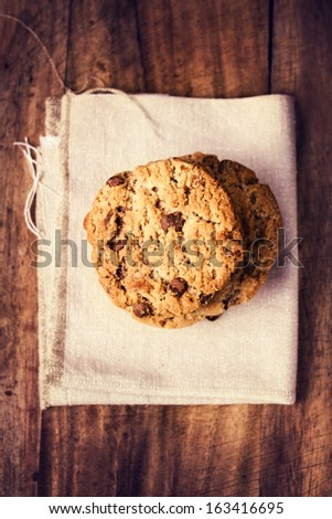 Stacked chocolate chip cookies on white linen napkin on wooden table in country style, top shot. - stock photo