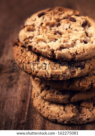 Stacked chocolate chip cookies on wooden background. Chocolate chip cookies shot with selective focus. - stock photo