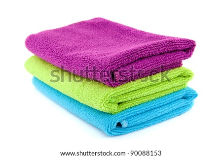 stacked colorful folded towels over white background