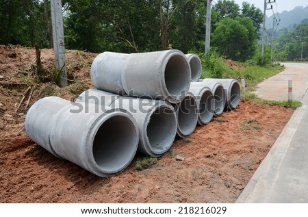 Stacked concrete drainage pipes - stock photo