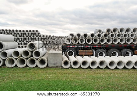 Stacked concrete pipes and loaded flatbed trailer - stock photo