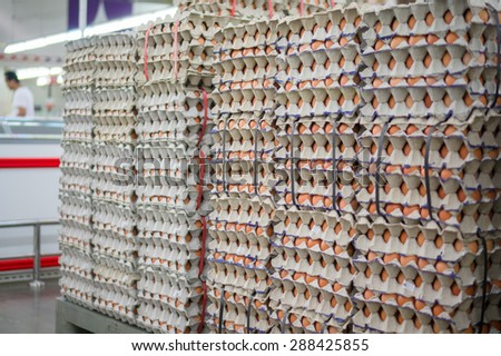 Stacked egges in trays in a rows in supermarket - stock photo