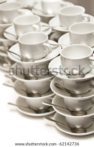 Stacked empty teacups with teaspoons at a function over white background - stock photo