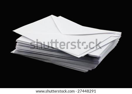 Stacked envelopes isolated on black - stock photo