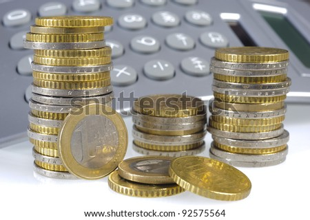 stacked euro coins and financial calculator - stock photo