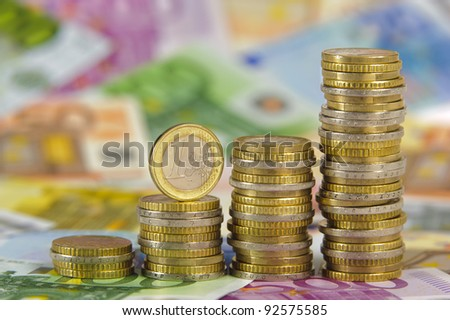 stacked euro coins on banknotes - stock photo