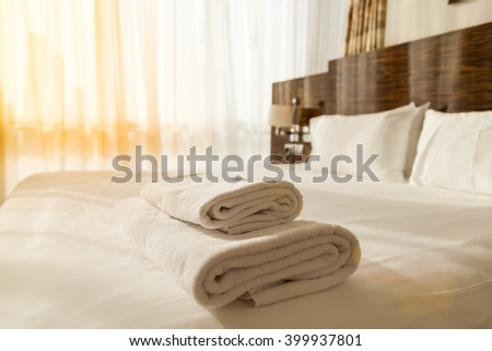 Stacked fresh white bath towels on the bed sheet. Close-up. Lens flair in sunlight - stock photo