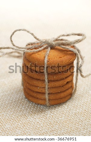 stacked ginger cookies tied by jute string on hessian background, shallow DOF - stock photo