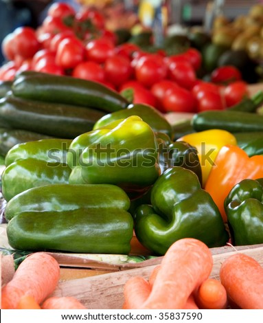 Stacked green, orange and yellow peppers, courgettes, tomatoes and carrots for sale at a vegetable market