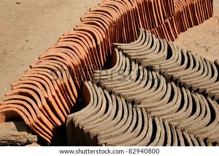 Stacked handmade clay roofing tiles - Kiln dried (orange) and non-fired tiles - stock photo
