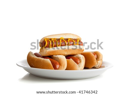 Stacked hot dogs with mustard and buns on a plate and a  white background - stock photo