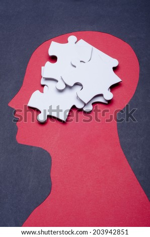 Stacked jigsaw puzzle pieces and black paper project as a outline of human head - stock photo