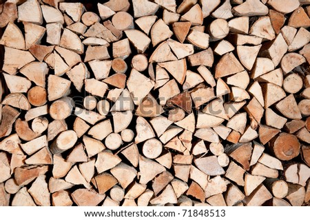Stacked logs of firewood - stock photo