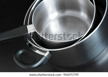 Stacked metal saucepans on dark background. - stock photo