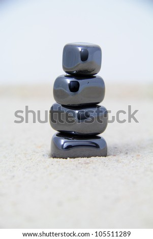 Stacked metallic stones on sand. - stock photo