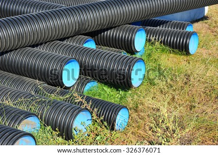 Stacked new PVC pipe on construction site - stock photo