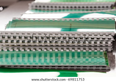 Stacked  notebooks in green color all over the desk. Hard light from window is reflected on covers. - stock photo