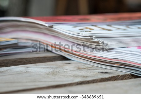 Stacked of magazines on wood table for reading pleasure background - stock photo