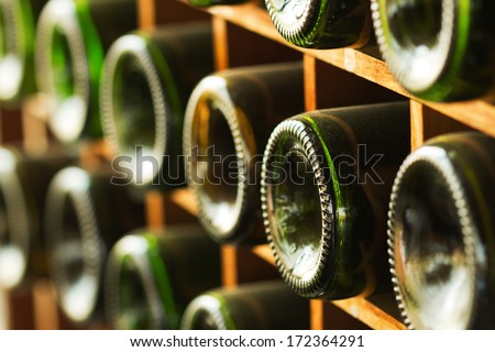 stacked of old wine bottles in the cellar,dusty but tasty - stock photo