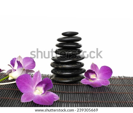 Stacked of stones and orchid on bamboo mat - stock photo