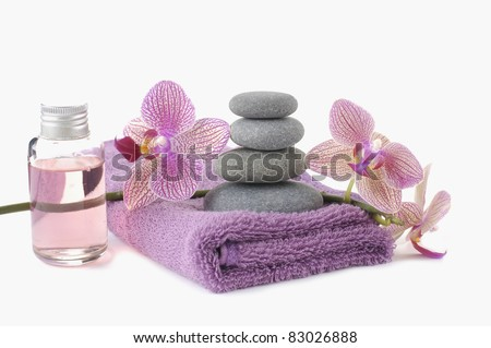 Stacked of Stones on pink spa towels and beautiful orchid with massage oil - stock photo
