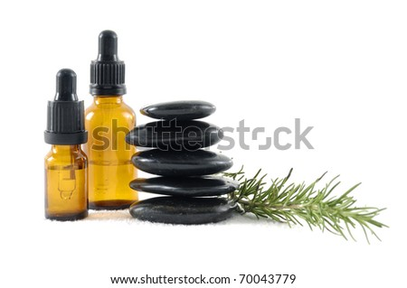 Stacked of stones with bottle of aromatherapy oil and fresh green leaves - stock photo