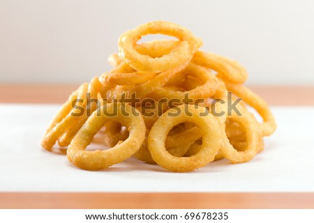 Stacked onion ring on a white waxed paper. Very shallow depth of field. - stock photo