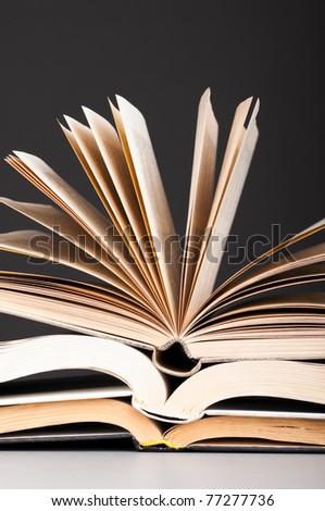 stacked open books on dark gray background - stock photo