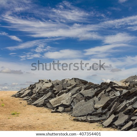 Stacked pieces of debris which was excavated asphalt demolition was left with the sky as a backdrop. - stock photo
