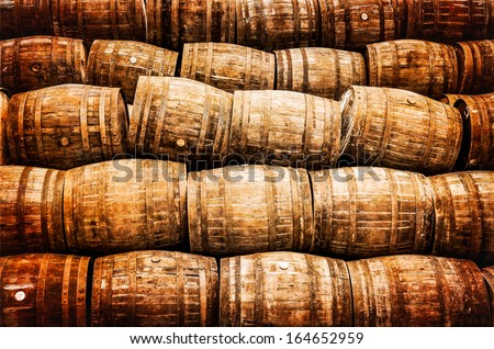 Stacked pile of old whisky and wine wooden barrels in vintage style - stock photo