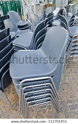 Stacked plastic chairs - stock photo